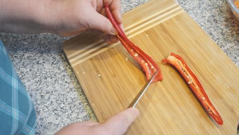 Разрезаем перчик пополам и удаляем из него семечки